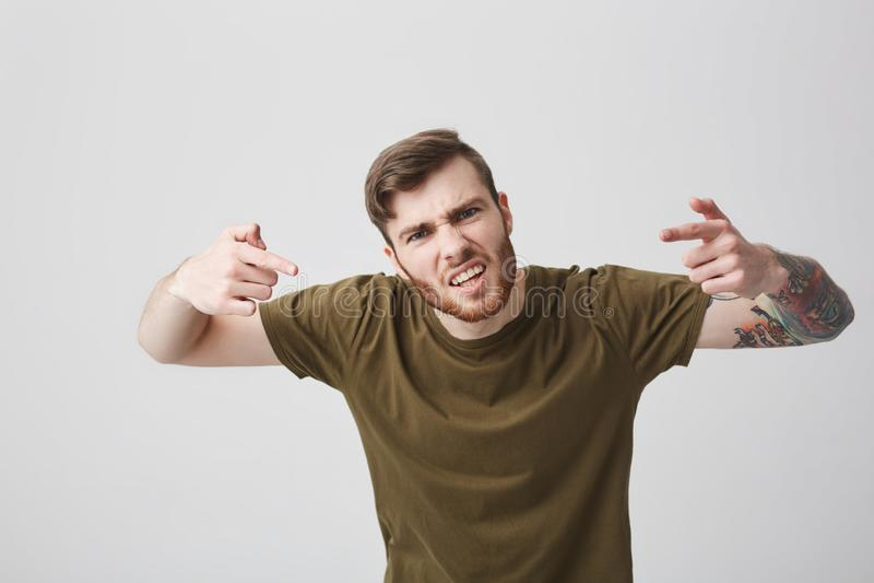Trek de bespreking van ` t aan me aan als dat, mens Portret van de jonge gebaarde aantrekkelijke agressieve mens met getatoeeerd  stock afbeelding