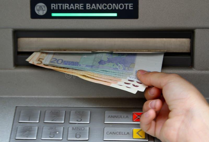 Trek geld in bankbiljetten van ATM terug stock foto's