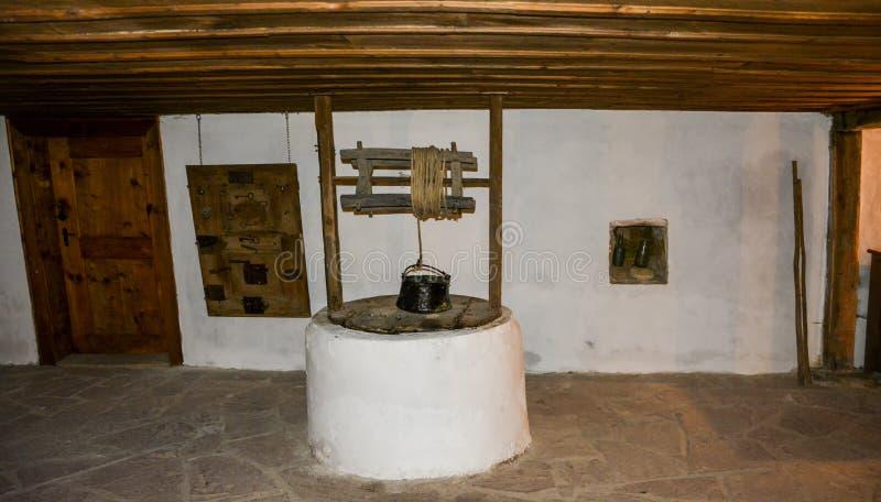 Trek goed onder een oud Bulgaars huis stock afbeeldingen