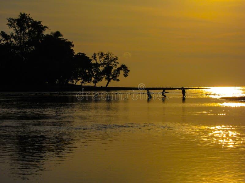 Trekkend in de dagenvangst, jonge vissers die bij zonsondergang samenwerken royalty-vrije stock afbeelding