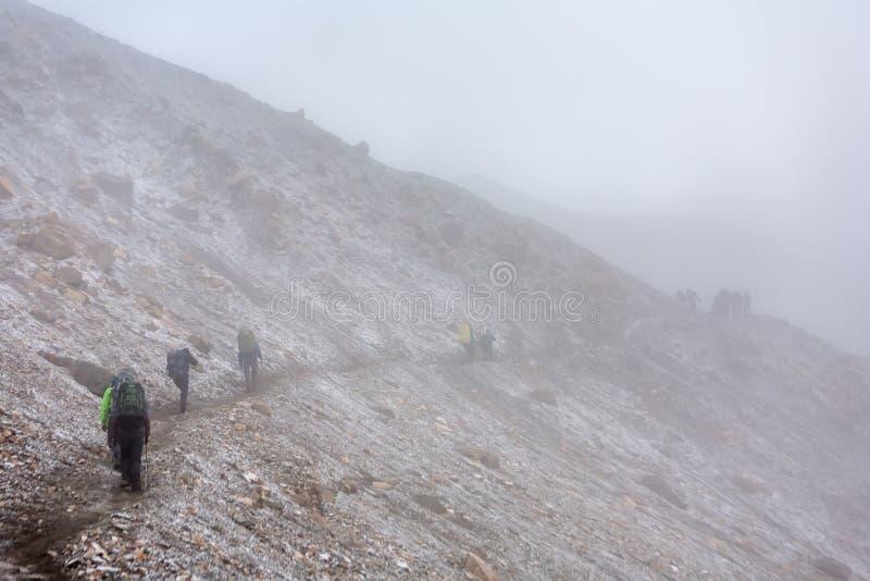 Trekker που περπατά αργά στο πέρασμα Λα Thorung - το υψηλότερο σημείο επάνω στοκ εικόνα