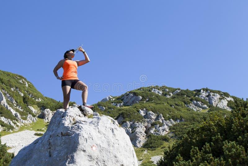 Trekker женщины выпивает высоко в горах стоковые фото