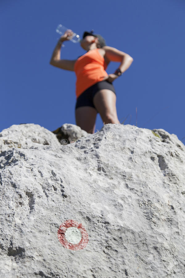 Trekker женщины выпивает высоко в горах стоковое изображение rf