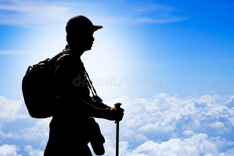 Trekker силуэта с рюкзаком, trekking поляком и камерой стоковые изображения