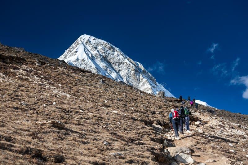 Trekker che si avvicina alla montagna di PumoRi in valle di Khumbu su un modo a immagine stock