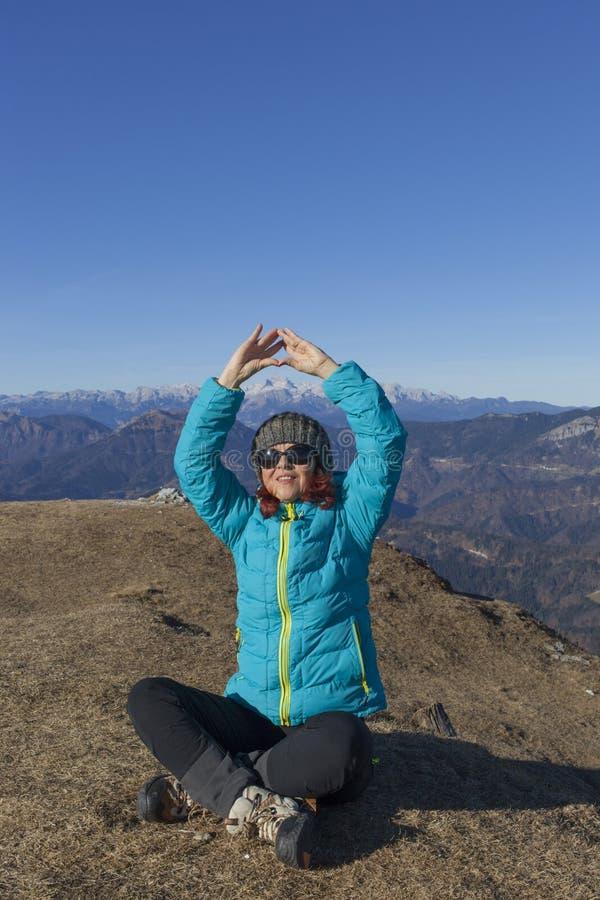 Trekker da mulher que relaxa nas montanhas foto de stock