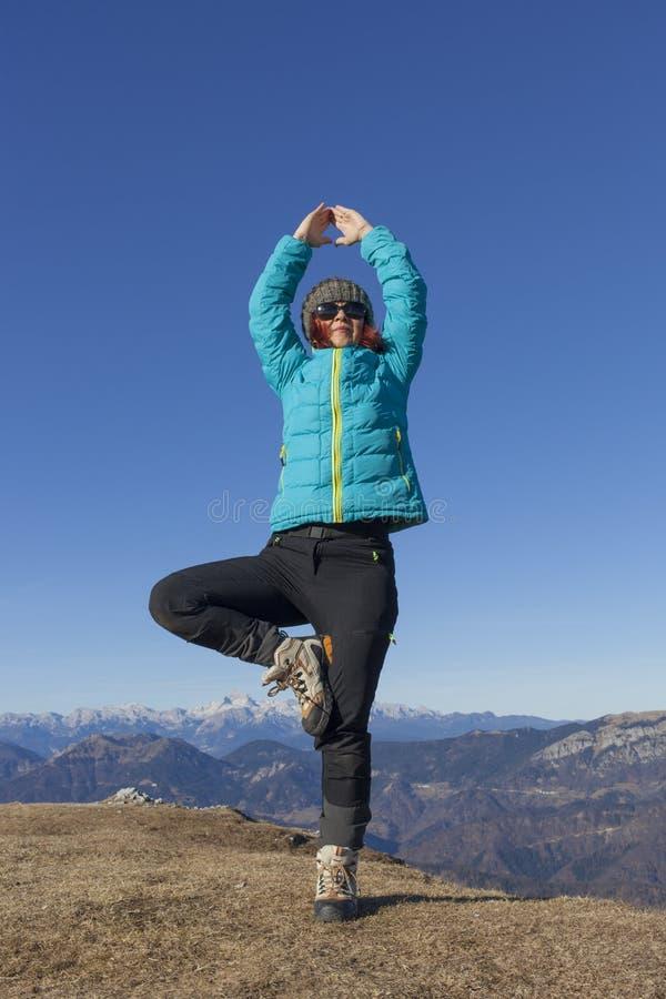 Trekker da mulher que relaxa nas montanhas imagem de stock