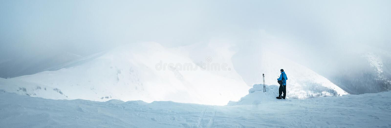 Trekker del invierno que permanece en pico de montaña que él subió y opinión amplia enjojing del panorame del valle cubierta por  imagenes de archivo