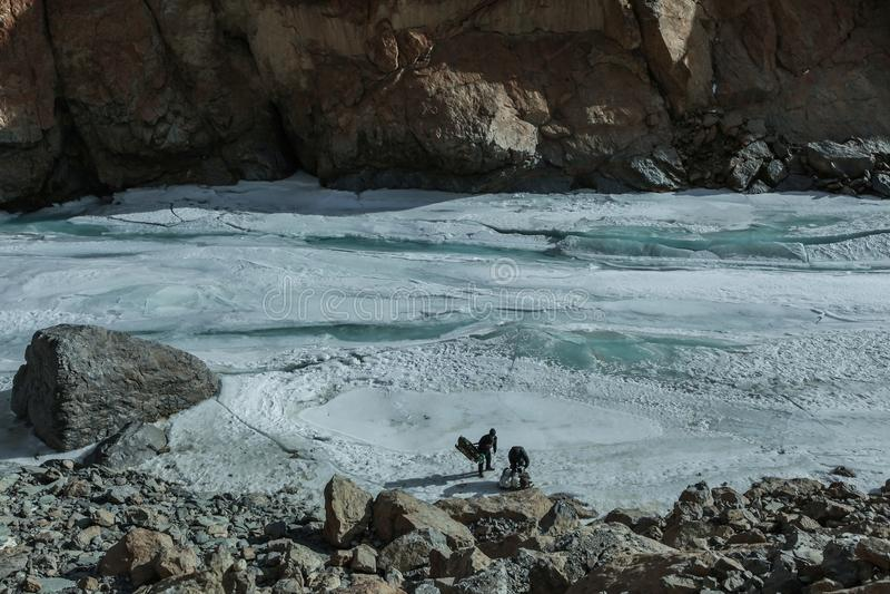 Trekker e porteiro que embalam seus equipamentos no duri congelado do rio fotos de stock royalty free
