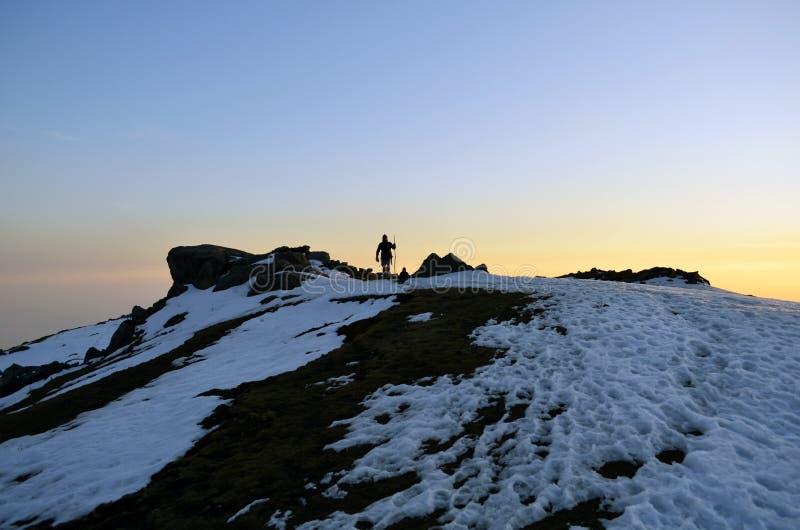 Trekker en Himalaya, líder que lleva el paquete al destino con puesta del sol en el contexto imagenes de archivo