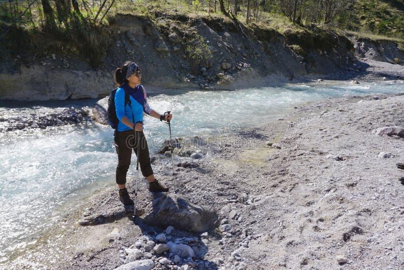 Trekker fêmea que está na borda do rio foto de stock