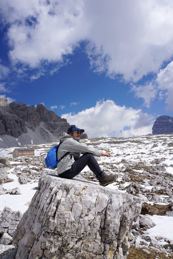 Trekker fêmea que senta-se na rocha com parte traseira bonita da paisagem imagens de stock