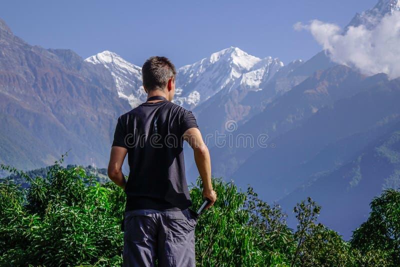 Trekker joven que mira el pico de la nieve fotografía de archivo