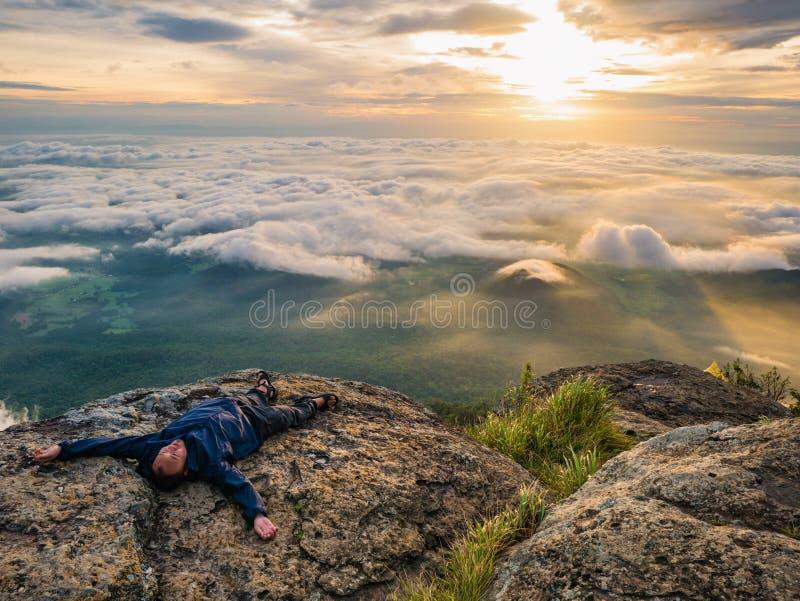 Trekker Kłaść puszek na falezie z Pięknym wschód słońca i morzem mgła w ranku na Khao Luang górze obraz stock