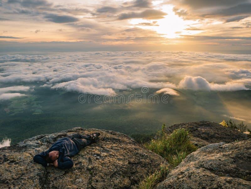 Trekker Kłaść puszek na falezie z Pięknym wschód słońca i morzem mgła w ranku na Khao Luang górze zdjęcia stock