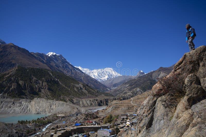 Trekker no penhasco olhando para a montanha, Annapurna Conservation Area, Nepal imagens de stock