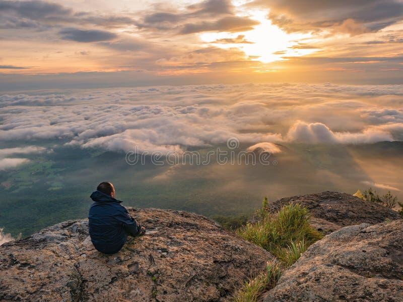 Trekker obsiadanie na górze z Pięknym wschód słońca i morzu mgła w ranku na Khao Luang górze obrazy stock