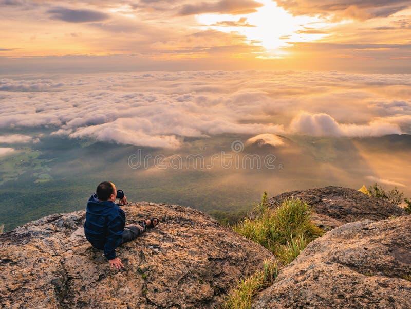 Trekker obsiadanie na górze z Pięknym wschód słońca i morzu mgła w ranku na Khao Luang górze zdjęcia royalty free