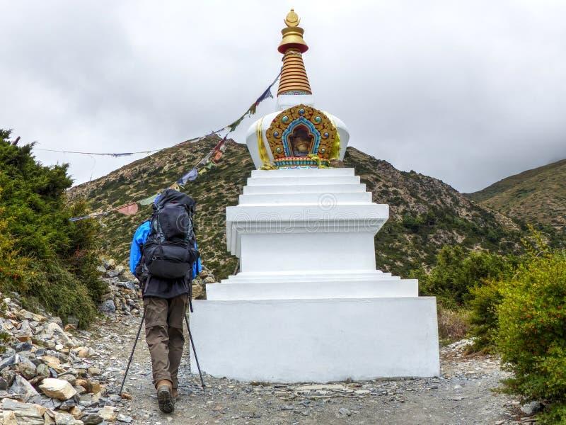 Trekker passing Stupa. Annapurna Circuit trek in Nepal, Marsyangdi river valley, near Ngawal village stock photo