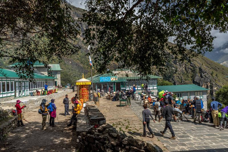trekker que camina en pueblo del verde de Khumjung cerca del bazar de Namche adentro imágenes de archivo libres de regalías