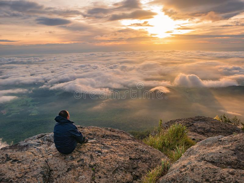 Trekker sitting on the mountain with Beautiful Sunrise and sea of mist in the morning on Khao Luang mountain. In Ramkhamhaeng National Park,Sukhothai province stock images