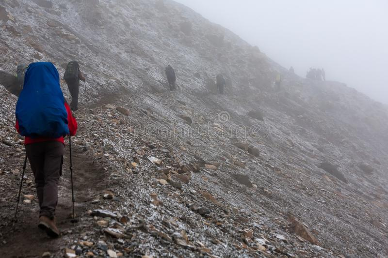 Trekker walking slowly to Thorung La pass - the highest point on Annapurna circuit in Nepal. Trekker at the Thorung La pass - highesr point of Annapurna circuit stock photography