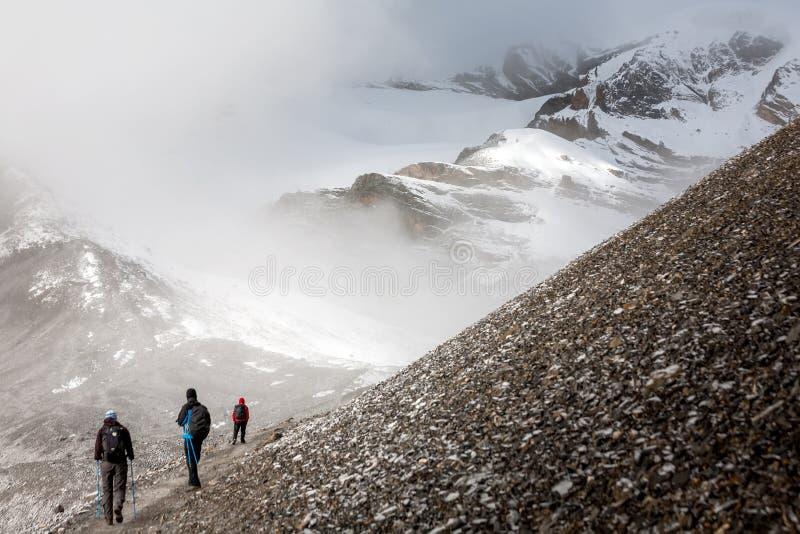 Trekker walking slowly to Thorung La pass - the highest point on. Annapurna circuit in Nepal stock image