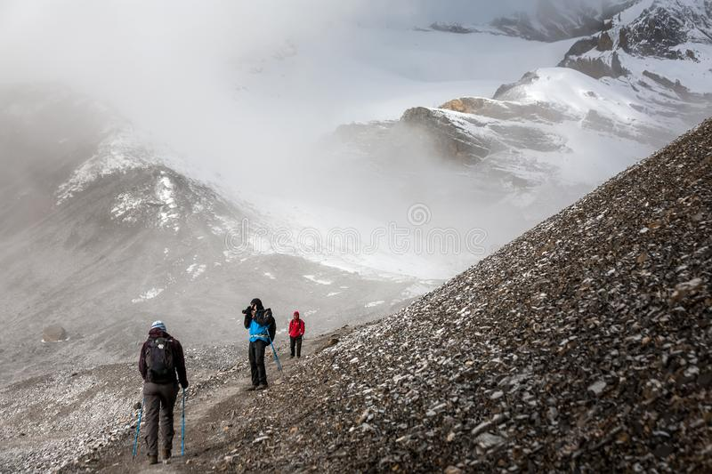 Trekker walking slowly to Thorung La pass - the highest point on. Annapurna circuit in Nepal royalty free stock photos