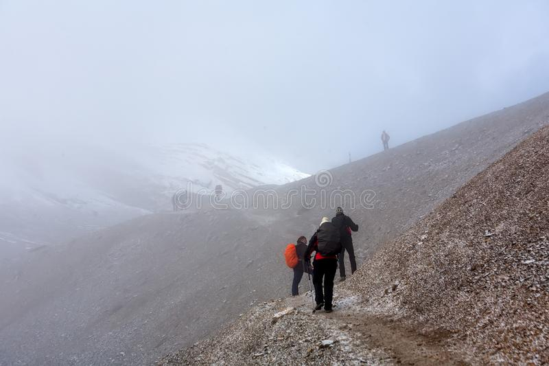 Trekker walking slowly to Thorung La pass - the highest point on. Annapurna circuit in Nepal royalty free stock photography