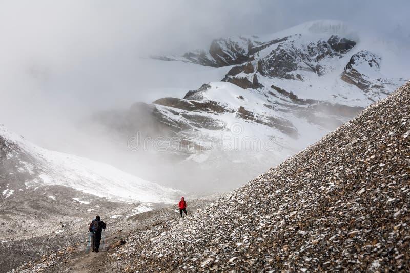 Trekker walking slowly to Thorung La pass - the highest point on. Annapurna circuit in Nepal stock photo