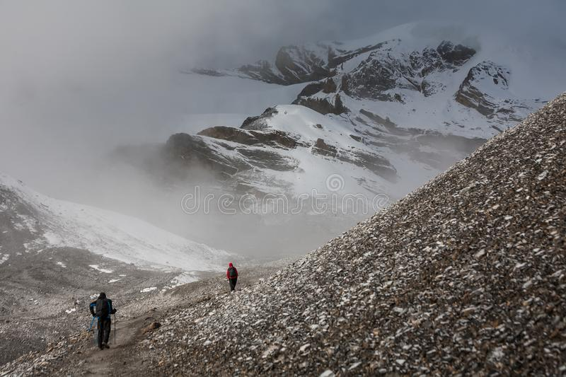 Trekker walking slowly to Thorung La pass - the highest point on. Annapurna circuit in Nepal royalty free stock image