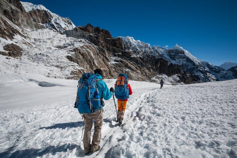 Trekkers пересекая Ла Cho проходят в зону Эвереста, Непал стоковое фото