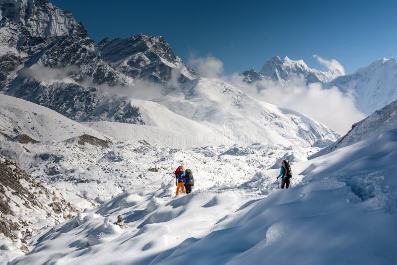 Trekkers пересекая ледник Gokyo в долине Khumbu на пути к Eve стоковые изображения