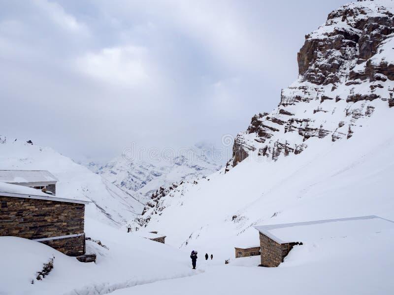 Trekkers che camminano sul passo di montagna della neve con le casette lungo la strada fotografie stock libere da diritti