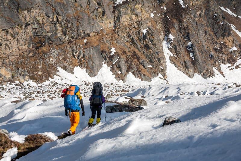 Trekkers die Gokyo-gletsjer in Khumbu-vallei op een manier kruisen aan Vooravond royalty-vrije stock afbeelding