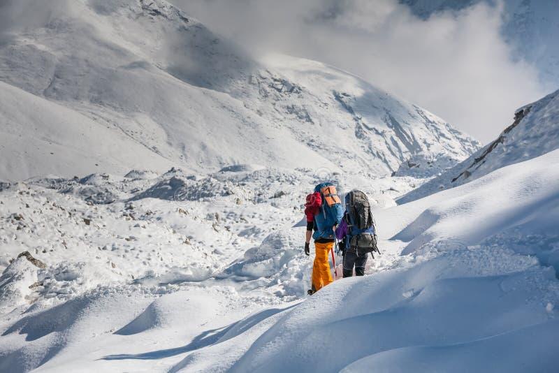 Trekkers die Gokyo-gletsjer in Khumbu-vallei op een manier kruisen aan Vooravond royalty-vrije stock foto's
