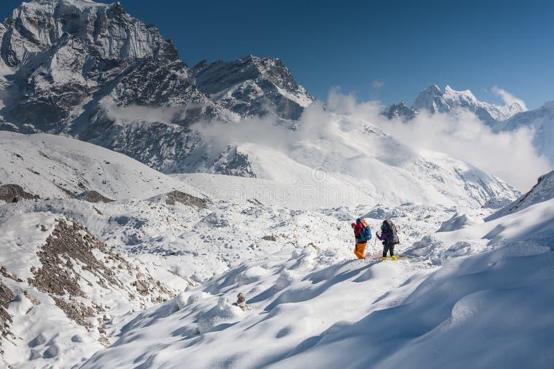 Trekkers die Gokyo-gletsjer in Khumbu-vallei op een manier kruisen aan Vooravond royalty-vrije stock foto
