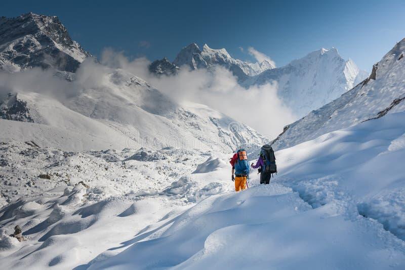 Trekkers die Gokyo-gletsjer in Khumbu-vallei op een manier kruisen aan Vooravond royalty-vrije stock afbeeldingen