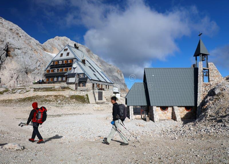 Trekkers perto da cabana de montanha de Kredarica e a capela dedicada à Nossa Senhora das Neves na Eslovênia fotos de stock