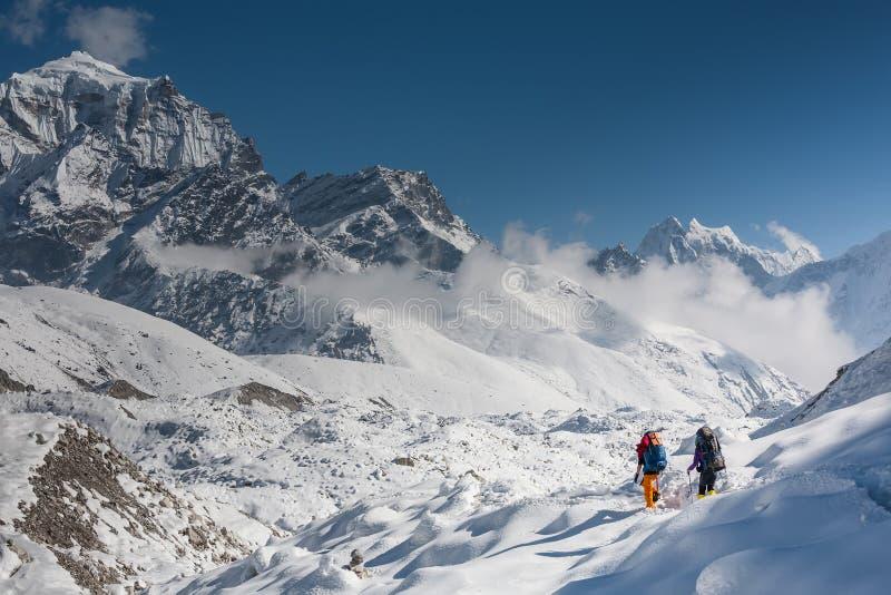 Trekkers que cruzam a geleira de Gokyo no vale de Khumbu em uma maneira à véspera foto de stock