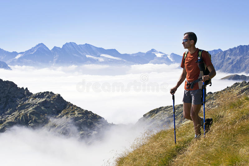 Trekking in the Alps. Man trekking in the Alps over the clouds in a beautiful sunny day. Gran Paradiso National Park, Italy stock images