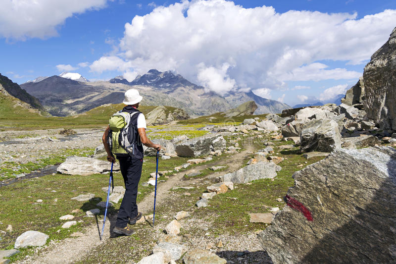 Trekking in the Alps. Man trekking in the Alps in a beautiful sunny day. Gran Paradiso National Park. Italy stock image