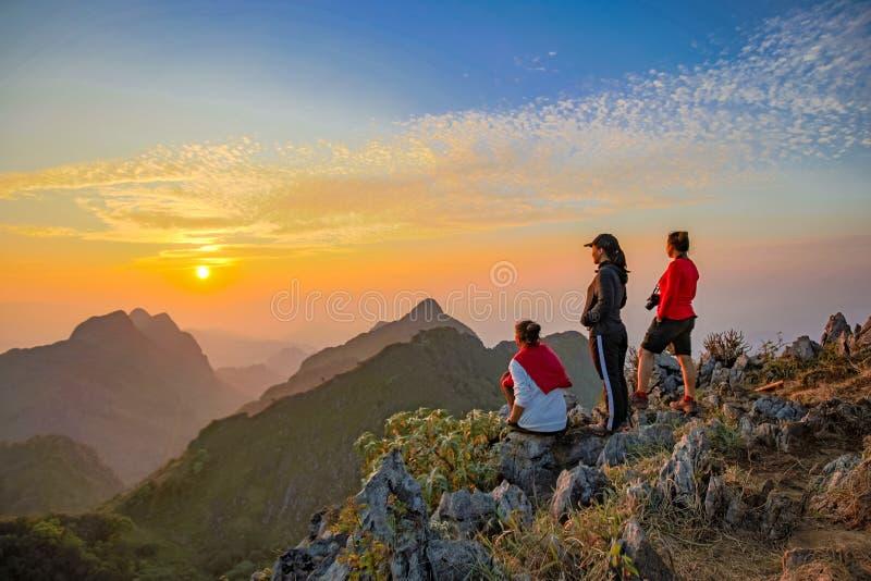 Trekking asiatico di viaggiatore con zaino e sacco a pelo tre che agisce sopra la nuvola dorata immagini stock libere da diritti