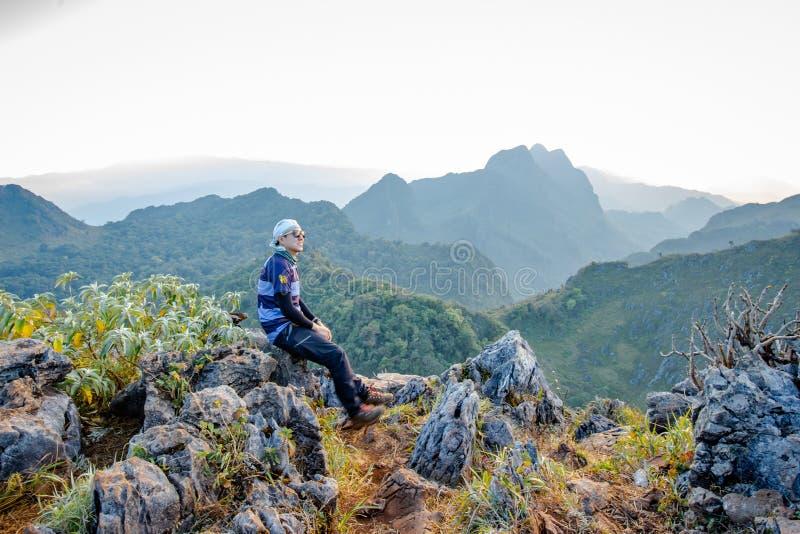 Trekking asiatico di viaggiatori con zaino e sacco a pelo che aspetta il cielo dorato di tramonto fotografie stock