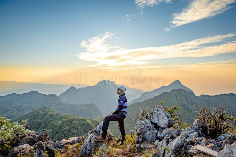 Trekking asiatico di viaggiatori con zaino e sacco a pelo che aspetta il cielo dorato di tramonto fotografia stock libera da diritti