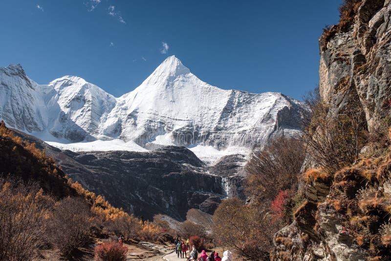 Trekking auf Herbsthügel mit heiligem Berg Yangmaiyong und blauem Himmel lizenzfreie stockbilder