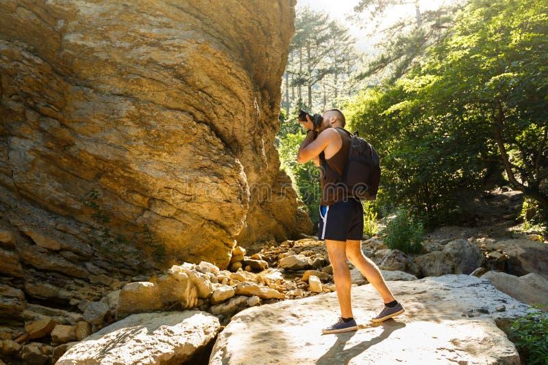 Trekking barbu d'homme de photographe parmi la forêt et les montagnes et photos de prise avec l'appareil-photo de dslr Forme hori photographie stock libre de droits