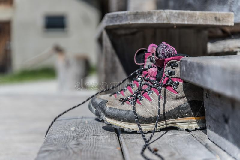 Trekking boots on the veranda of an alpine hut. Summer holidays in the mountains. Close up picture of hiking boots on a rustic wooden veranda of an alpine hut royalty free stock photo