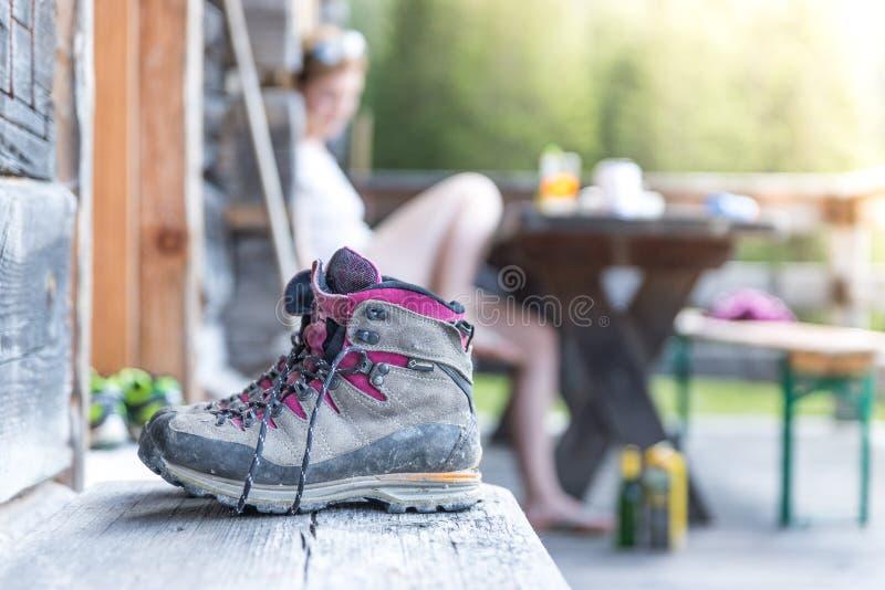Trekking boots on the veranda of an alpine hut. Summer holidays in the mountains. Close up picture of hiking boots on a rustic wooden veranda of an alpine hut stock photos