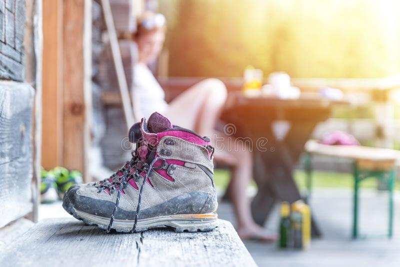 Trekking boots on the veranda of an alpine hut. Summer holidays in the mountains. Close up picture of hiking boots on a rustic wooden veranda of an alpine hut stock photography